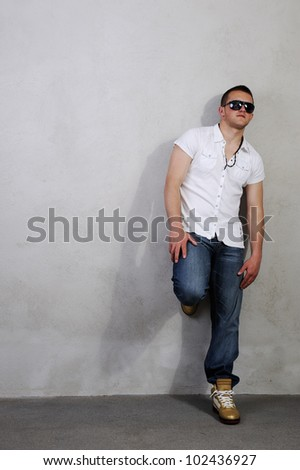 Man in dark glasses leaning on the wall