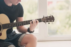 Man in denim shorts sitting next to the window with his guitar music, musician, hobby, lifestyle, hobby