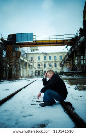 Man in depression sitting on rail in factory