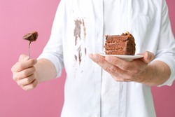 Man in dirty clothes eating chocolate cake on color background, closeup