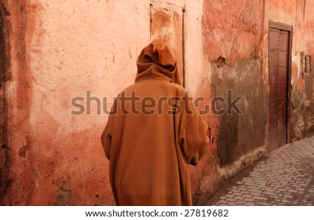 Man in djelleba walking in a orange brown street in Marrakesh,Morocco