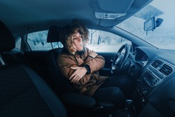 Man in down jacket tries to keep warm and not freeze in his stalled car in winter. The concept of a dangerous accident or heater failure in the cold season
