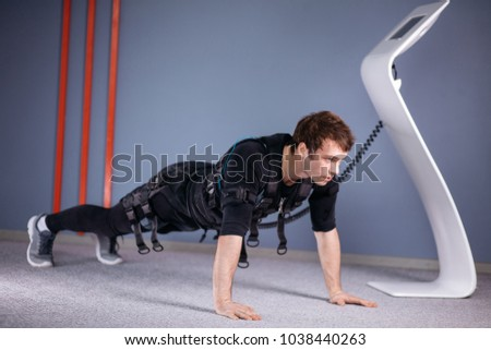man in Electrical Muscular Stimulation suits doing plank exercise. EMS. Workout. #1038440263