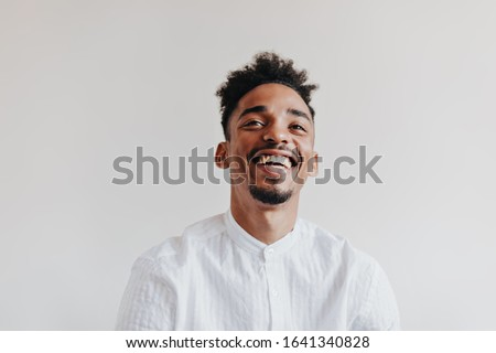 Man in excellent mood genuinely laughs on white background. Cheerful guy in white shirt smiling on isolated backdrop Foto stock ©