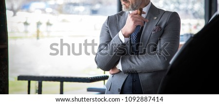 Man in expensive custom tailored suit posing and holding a cigar