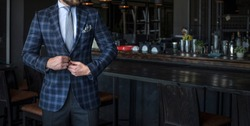 Man in expensive custom tailored suit standing and posing inside of a bar