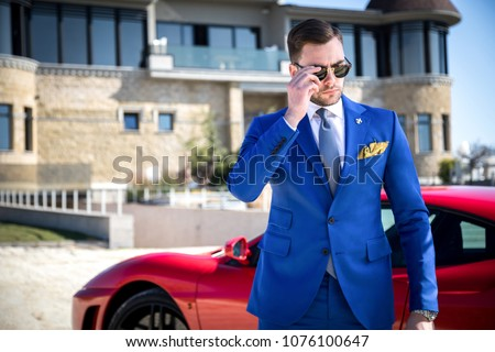 Man in expensive custom tailored suit with glasses posing outdoors in front of expensive car and house Stock photo ©