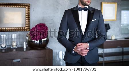 Man in expensive custom tailored tuxedo, suit posing indoors