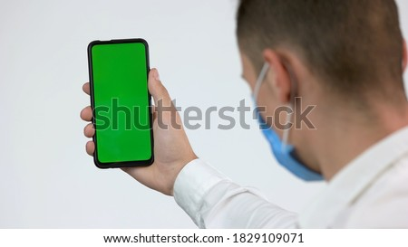 Photo of  Man in face mask looks at green phone screen. Back view man wearing protective medical mask and looks at the green empty smarthone screen. Chromakey, copy space.
