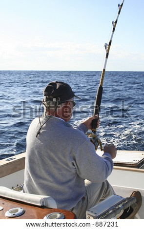 Man in Fighting Chair Reeling in Gamefish