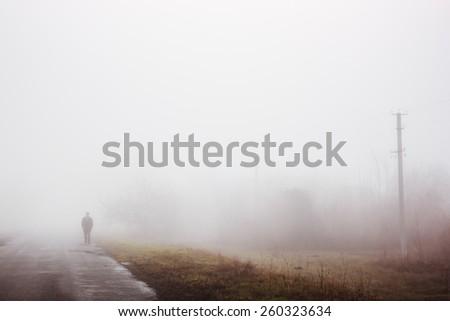 Man in fog. Silhouette of man walking on misty village road. Loneliness, nostalgia, sad mood