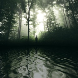 man in forest lake landscape with forest reflection on water surface