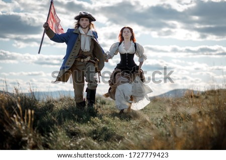 Man in form of officer of War of Independence and girl in historical dress of 18th century. July 4 is US Independence Day. Couple of patriots freedom fighters in outdoor on background cloudy sky Stock photo ©