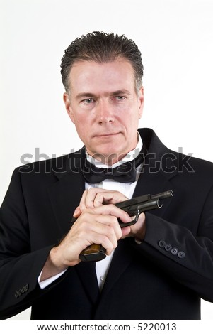 Man in formal attire, cocking a 9mm automatic weapon, taken in front a white background.