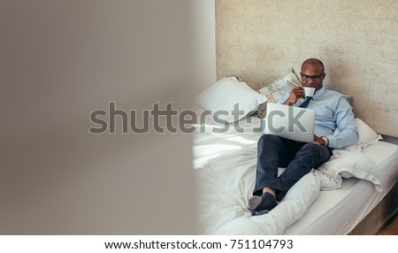 Man in formal clothes working on laptop while lying in bed. Businessman working on laptop computer while drinking coffee in his hotel room. #751104793