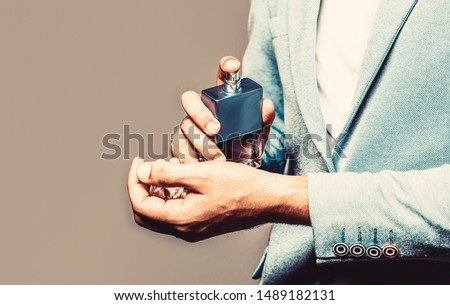 Man in formal suit, bottle of perfume, closeup. Fragrance smell. Men perfumes. Fashion cologne bottle. Man holding up bottle of perfume. Men perfume in the hand on suit background. Copy space. Foto stock ©