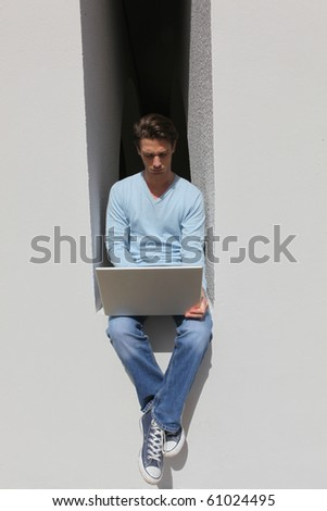Man in front of a laptop computer outdoors