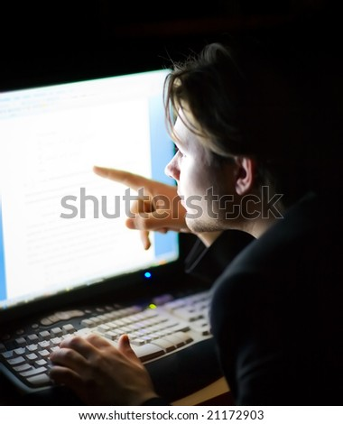 Man in front of computer screen. Dark night room.