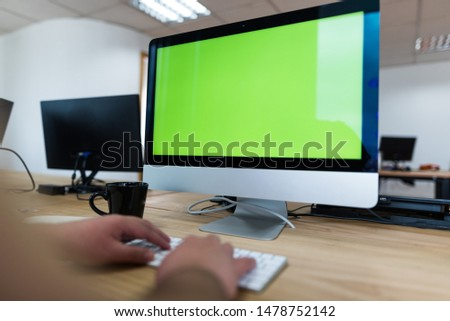 Man in front of computer screen typing on green screen, with keyboard and mouse next to coffee and more screens behind #1478752142