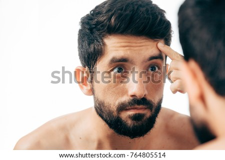 Man in front of mirrror looking at his wrinkles #764805514