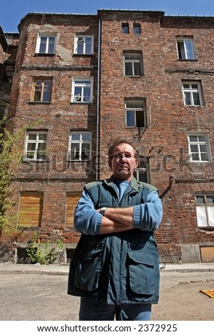 man in front of  ruined tenement-house in Warsaw, Poland