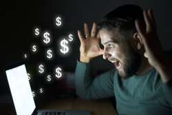 Man in front of the computer with raised hands get paid. Business and money concept. Dollars flying.