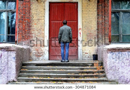 Man in Front of the Old House before the Closed Door
