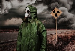 Man in gas mask and cloak for chemical protection on abandoned road with radiation area caution sing under heavy clouds. Nature protection concept