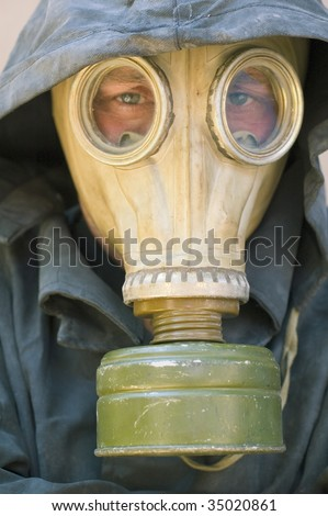 man in gas mask and dirty waterproof cape-tent with hood