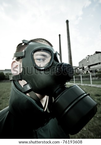 man in gas mask on smoky industrial background with pipes