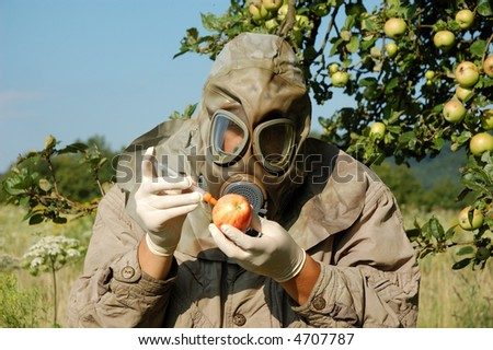 Man in gas mask preparing contaminated apples