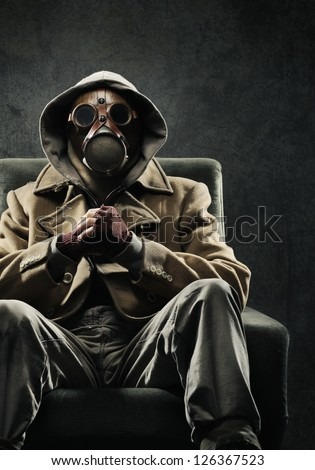 Man in gas mask sitting in a chair