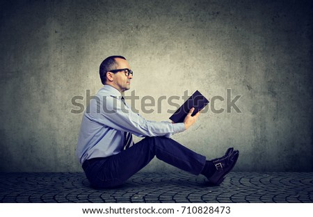 Man in glasses reading a book #710828473