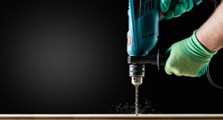 Man in Gloves Drilling wooden plank by Green Drill, close-up. Copy space.