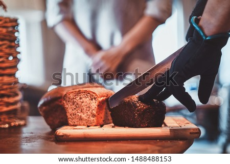Man in gloves is slicing tasty loaf for lunch at small artisan caffeteria.