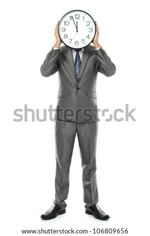 man in gray suit holding big clock covering his face. isolated over white background