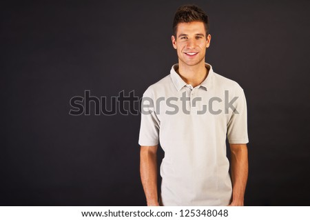 Man in grey polo t-shirt on black background with smile