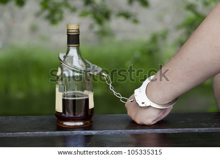 Man in handcuffs interconnected with a bottle of alcohol
