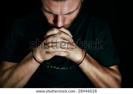 Man in handcuffs praying
