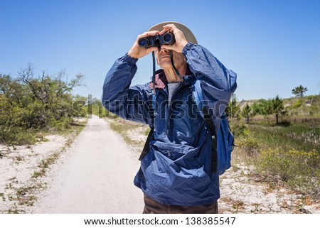 Man in hat, backpack and windbreaker standing on a path in a national park, looking through binoculars.