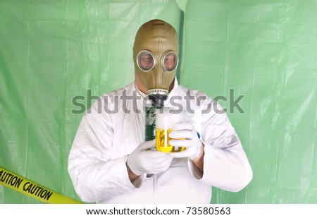 Man in Hazmat clothing in temporary green plastic decontamination chamber wearing a gas mask and carrying toxic chemical that is exuding gaseous vapor - stock photo