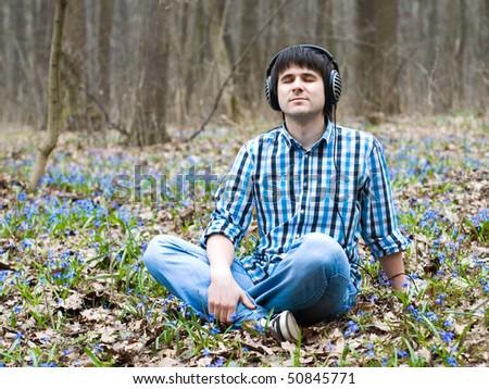 Man in headphones listening music in spring flowers
