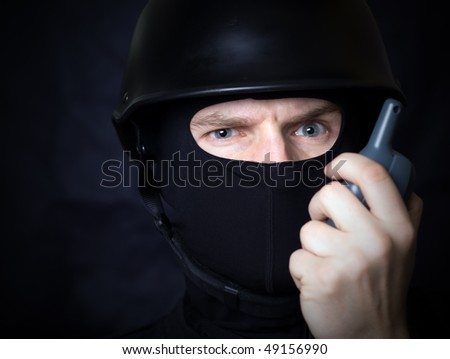Man in helmet and mask communicate by walkie-talkie radio. Might be a terrorist with bomb detonator