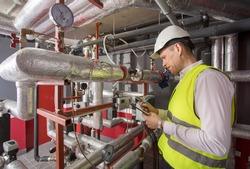 Man in helmet writing down measurements in boiler room