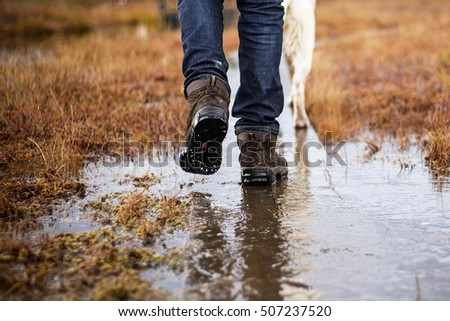 Man in hiking boots and jeans walking with dog in swamp