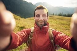 Man in hiking gear taking a selfie outside