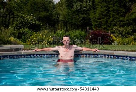 Man in his fifties relaxing in a pool in a backyard garden