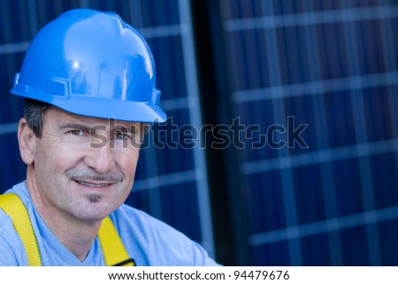 Man in his forties overseeing a Solar Installation in front of Solar panels