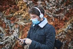 Man in his 40s with a mask to protect himself from Coronavirus, Covid-19, checks his phone while listening to music with his headphones. Concept of safety and positivism.