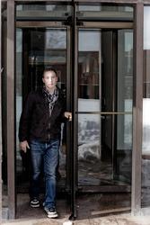 Man in his twenties walks through a revolving doorway entrance.